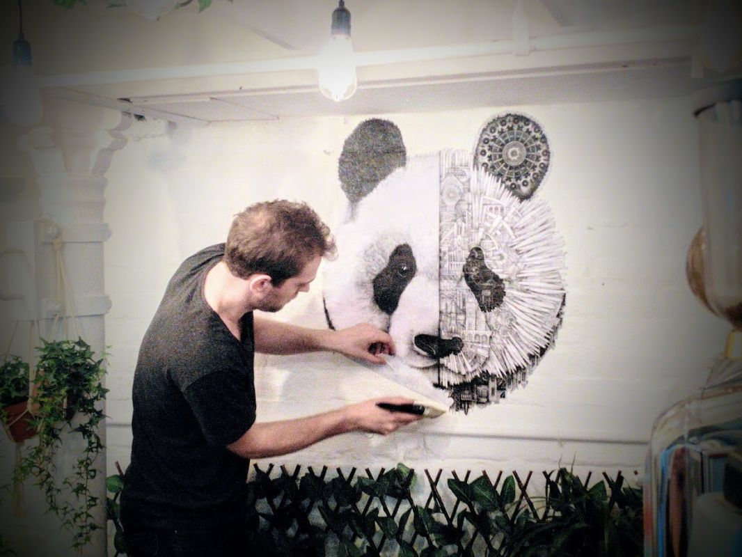 French artist Ardif installing a paste-up at Long and Short coffee shop in Brick Lane